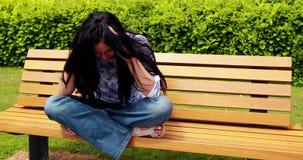 Pensamiento moreno triste en banco en el parque almacen de metraje de vídeo