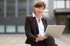 Pensamiento que se sienta de la empresaria con su ordenador portátil Imagen de archivo libre de regalías