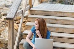 Pensamiento que se sienta de la mujer con su ordenador portátil Imágenes de archivo libres de regalías