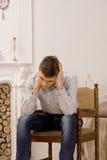 Pensamiento que se sienta del hombre joven en la sala de estar Fotografía de archivo libre de regalías