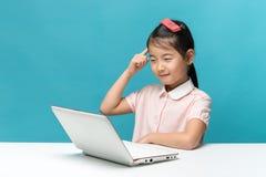 Pensando, bambina sveglia dell'Asia che gode del computer portatile su fondo blu Immagine Stock Libera da Diritti