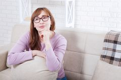 Pensant et rêvant la femme de Moyen Âge détendant à la maison Copiez l'espace et raillez  Foyer sélectif ménopause la fleur de jo Images stock