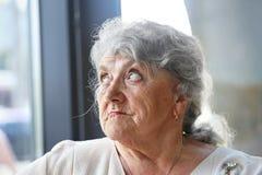 Pensativo y mirando la cara de la abuela imagenes de archivo