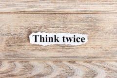 Pense duas vezes o texto no papel A palavra pensa duas vezes no papel rasgado Imagem do conceito Foto de Stock