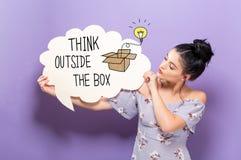 Pense fora da caixa com a mulher que guarda uma bolha do discurso imagens de stock royalty free