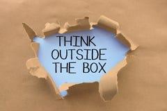 Pense fora do provérbio ou do conselho da caixa escrito à mão na página branca, atrás do papel marrom ou do cartão rasgado fotos de stock royalty free
