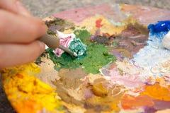 Penseel dat kleuren op palet mengt Royalty-vrije Stock Foto's