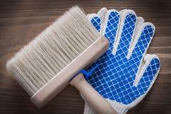Penseel en beschermende handschoenen op uitstekende houten mede achtergrond Stock Fotografie