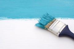 Penseel met blauwe verf, die over witte raad schilderen stock foto