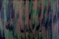 Penseldrag med tjock målarfärg i skuggor av gräsplan, blått, lilor på gammal trätextur Royaltyfri Bild