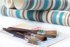 Penselen, behang, en kleurenmonster stock foto's
