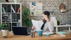Penser de soupir d'employé de bureau de documents malheureux de lecture au problème au travail clips vidéos