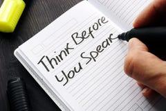 Pensez avant que vous parliez manuscrit sur une note image stock
