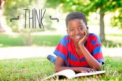Pensez contre la lecture de petit garçon en parc Photos stock