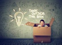 Pensi fuori del concetto della scatola Giovane donna che esce da scatola fotografie stock