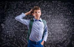 Pensiero del ragazzo, graffiante la sua testa, lavagna con matematico Immagine Stock Libera da Diritti