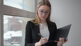 Pensiero dell'imprenditore della giovane donna e documento di affari di scrittura vicino alla finestra stock footage