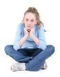 Pensiero di seduta della bella ragazza teenager sopra il bianco Immagini Stock