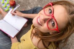 Pensiero di seduta della studentessa mentre studiando fotografia stock