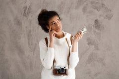 Pensiero femminile africano della fotografia, tenente soldi sopra fondo beige Fotografia Stock Libera da Diritti