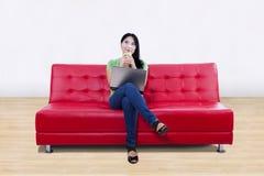 Pensiero femminile asiatico sul sofà rosso con il computer portatile alla h Fotografie Stock