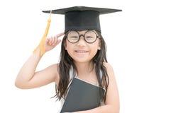 Pensiero laureato e sorriso del bambino asiatico della scuola con il cappuccio di graduazione Fotografia Stock