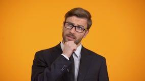 Pensiero maschio pensieroso alle idee di affari per l'inizio su, fondo arancio stock footage