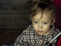 Pensieve kleines Baby, das in einem Spaziergänger sitzt Stockfoto