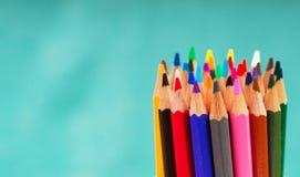 Pensils multicolores en la caja en un fondo azul Imagen de archivo