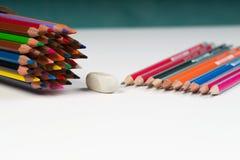 Pensils y elástico multicolores en la caja en el papel Fotografía de archivo libre de regalías
