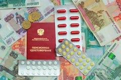 Pensioencertificaat, pillen en geld stock afbeeldingen