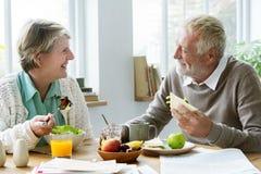 Pensionäråldringpar som äter frunchbegrepp Arkivfoton