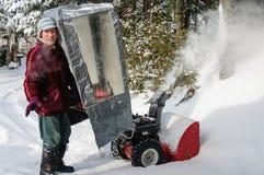 Pensionär bak snöblåsare royaltyfri fotografi