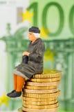 Pensionär, der auf Bargeldstapel sitzt Lizenzfreie Stockfotografie