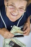 Pensionär, der Geldbörse mit Geld hält lizenzfreie stockfotografie