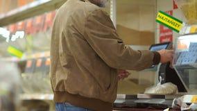 Pensionär, der Getreide auf den Skalen im Supermarkt wiegt Einsamer alter Mann, Lebensmittelgeschäftabteilung stock video footage