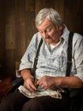 Pensionär, der sein Rohr vorbereitet Stockfotos