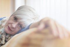 Pensionär i fönsterljus Royaltyfri Bild