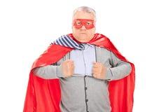 Pensionär i superherodräkten som river hans skjorta Arkivfoto