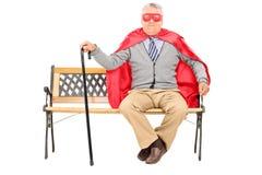 Pensionär i superherodräktsammanträde på en bänk Royaltyfri Bild