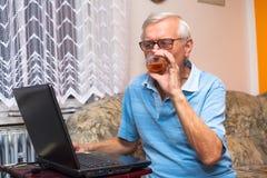 Pensionär med bärbara datorn och exponeringsglas av whisky Arkivbild
