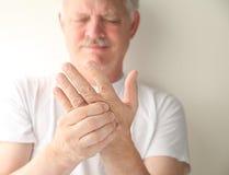 Pensionär med den numb handen Fotografering för Bildbyråer