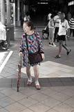 Pensionär med en maskeradkläder, MRT-station, Singapore Arkivbilder