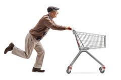 Pensionär med exponeringsglas som 3D kör och skjuter en tom shoppingbil Arkivfoton