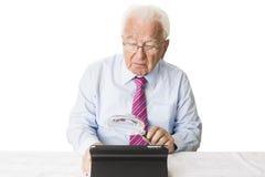 Pensionär med minnestavlan och förstoringsglaset Arkivfoton