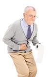 Pensionär med papper för toalett för mageknip hållande Arkivbild