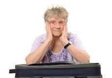 Pensionär med resväskor Arkivfoto