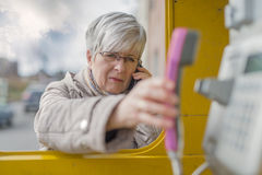 Pensionär med Smartphone och telefonluren Arkivfoton