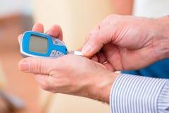 Pensionär med sockersjuka genom att använda analysatorn för blodglukos Arkivbild