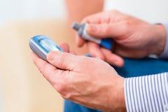 Pensionär med sockersjuka genom att använda analysatorn för blodglukos Arkivfoto